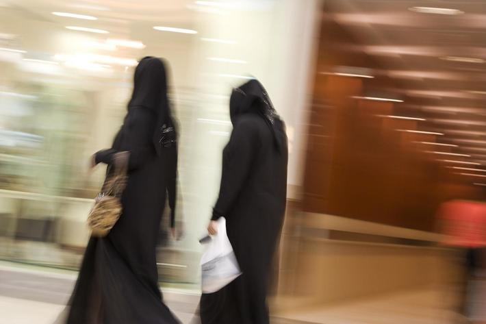 Dubai, UAE, Two women dressed in traditional abayas and hijabs, black robes and scarves.