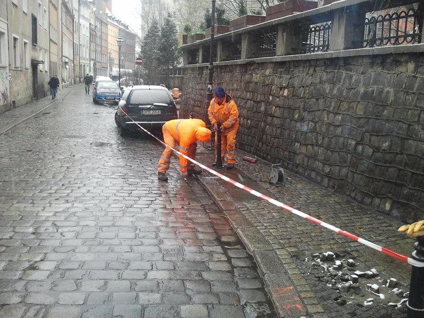 Robotnicy ustawiają słupki na chodniku przy ul. Szajnochy