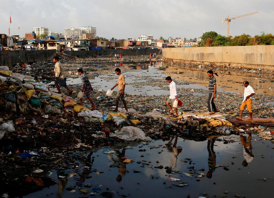 Residents cross a polluted water canal at a slum on the World Environment Day in Mumbai