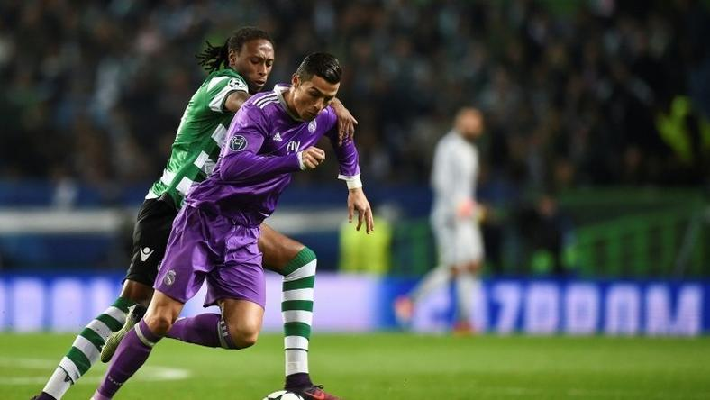 Real Madrid's forward Cristiano Ronaldo (R) clashes with Sporting's defender Ruben Semedo on November 22, 2016