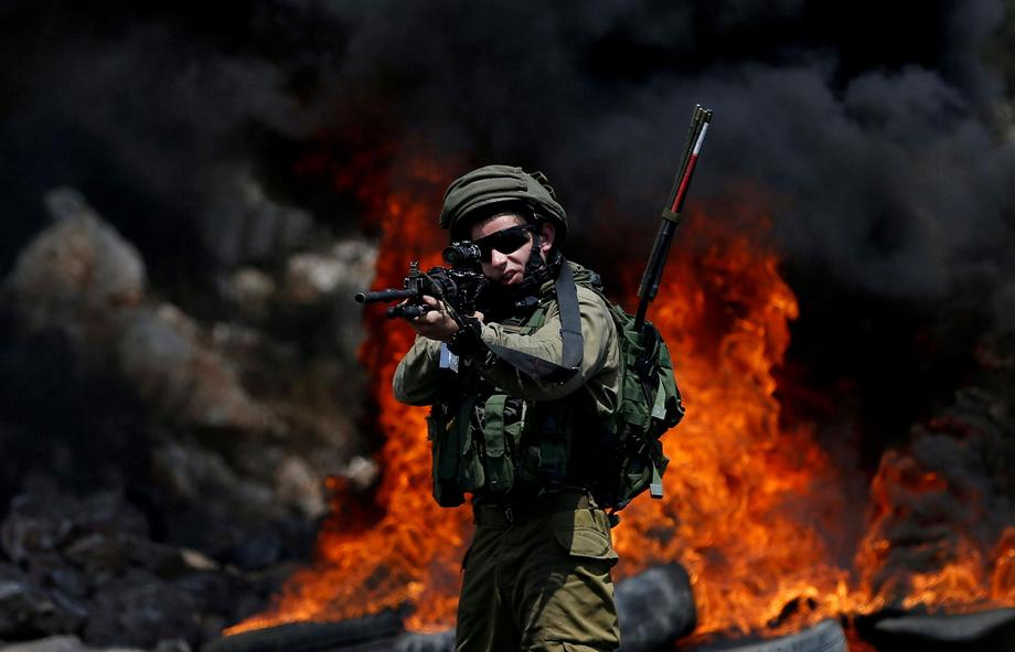 An Israeli soldier walks points his weapon toward Palestinian protesters during clashes in the West