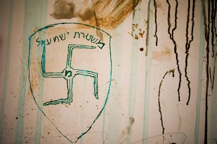 "A swastika and text in Hebrew reading ""Israeli police"" are seen on a wall of a synagogue after it wa"