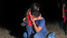 An immigrant father and daughter embrace after crossing the border from Mexico on August 13, 2021 in Roma, Texas.