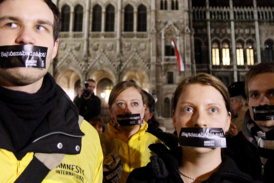 Hungarians, with stickers on their mouth, take part in a demonstration against the government's new
