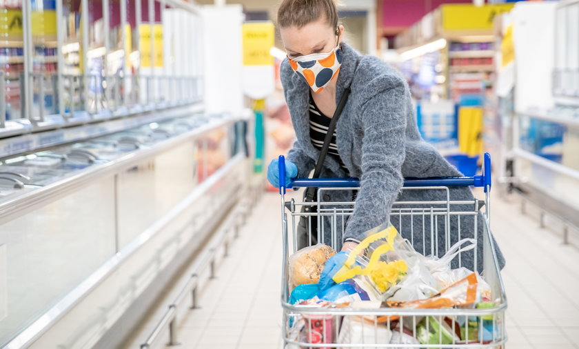 woman shopping for groceries in a supermarket during a coronavirus epidemic with a medical mask on h