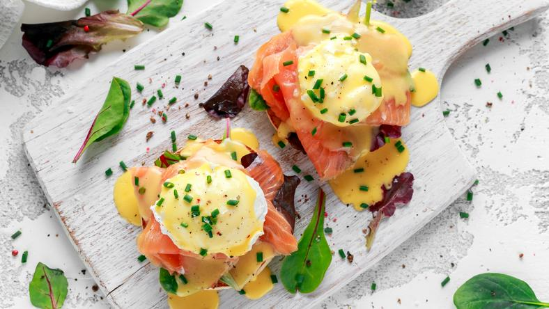 Eggs Benedict on english muffin with smoked salmon, lettuce salad mix and hollandaise sauce on white
