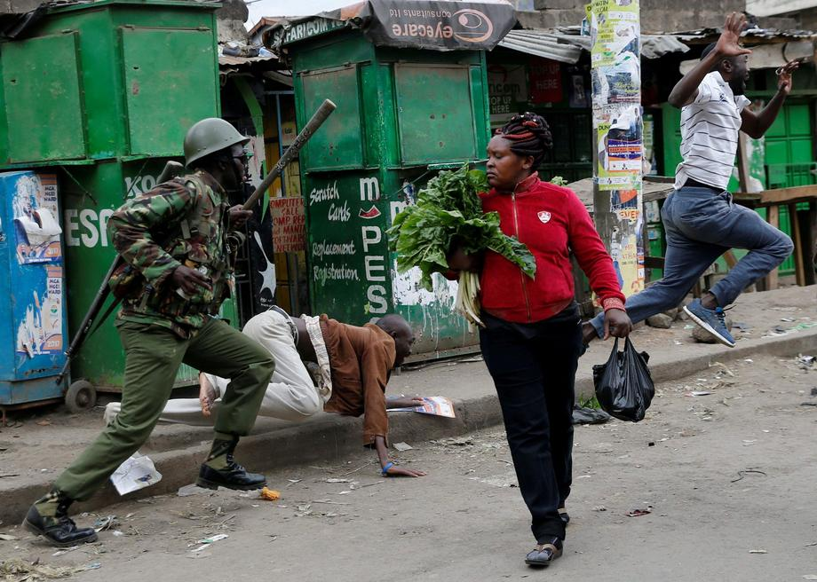 An anti riot policeman attempts to disperse people from the street as a woman carrying vegetables wa