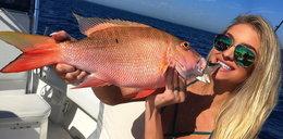 Piękność pręży się przy olbrzymich rybach. To jej hobby