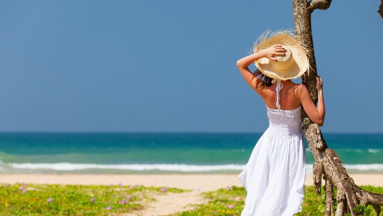 Kobieta w letniej białej sukience. Plaża. Morze. Urlop. Wakacje