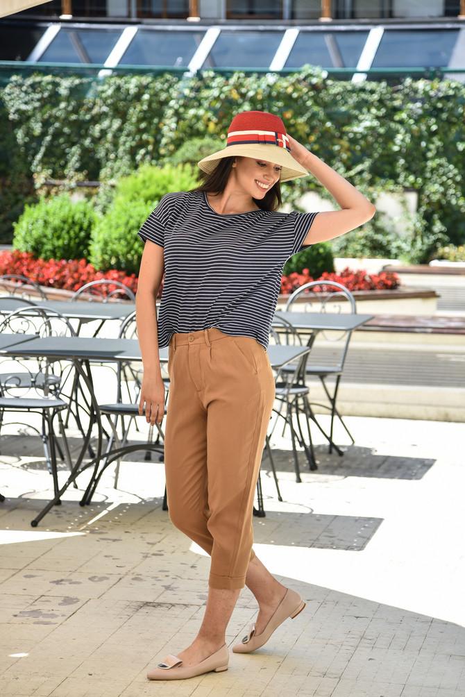 """Mornarska majica na trendi način   Prugastu majicu u mornarskom stilu umesto uz bele, teget ili crvene pantalone, kako smo svi navikli, ponesite uz bež. Umesto opuštene mornarske kombinacije dobićete sofisticiranu dnevnu.Majica i pantalone """"Oviesse"""", 2.190 i 3.490 din, šešir """"Tiffany"""", 1.290 din, cipele BN BOS, 9.900 din"""