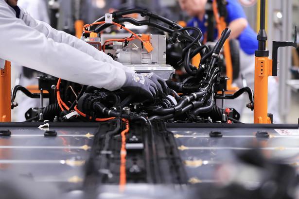 Pracownik fabryki Volkswagena w Zwickau podłącza akumulator litowo-jonowy do silnika elektrycznego w modelu ID.3. Niemcy, 25.02.2020