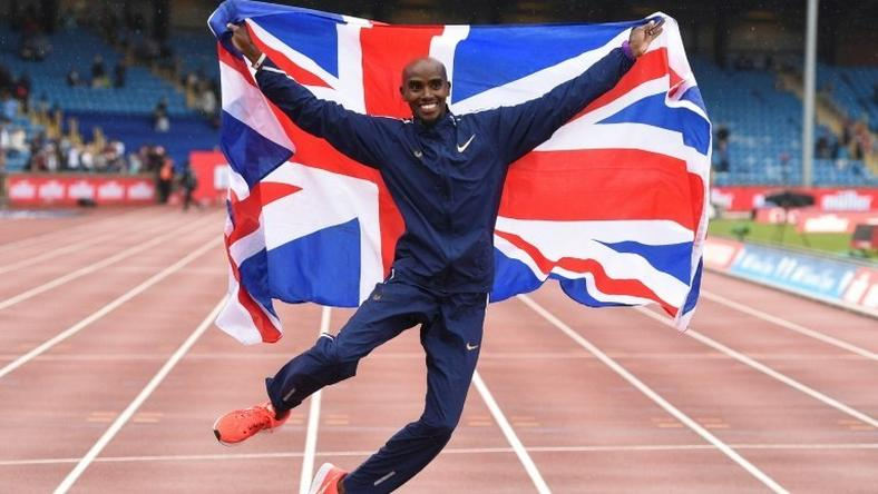 Britain's Mo Farah poses with a national flag after winning the men's 3,000m during the 2017 IAAF Birmingham Diamond League athletics on August 20, 2017