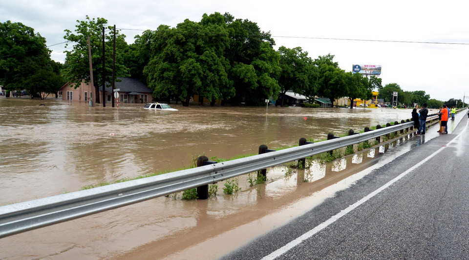 People stand on an interstate highway as flood water covers the roads businesses and houses in San Marcos Texas