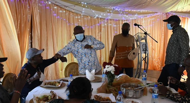 Guests eating at Kieni MP Kanini Kega's home during an event to celebrate his son's rite of passage