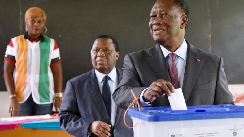 Ivory Coast's President Alassane Ouattara (R) casts his ballot in the presidential election where he seeks a new term on December 18, 2016