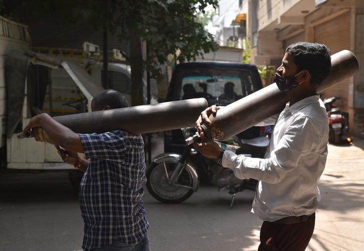 Oxigénpalackot cipelő helyiek Indiában / EPA/IDREES MOHAMMED