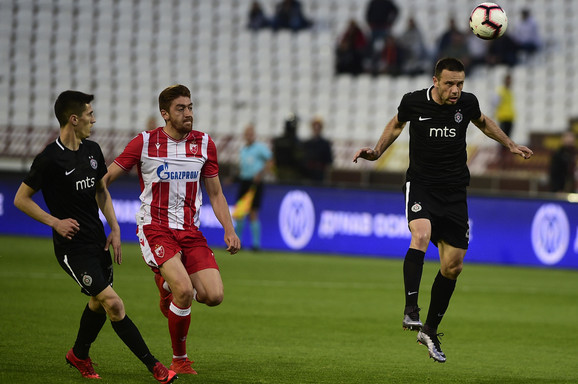 Milan Pavkov između dva igrača Partizana