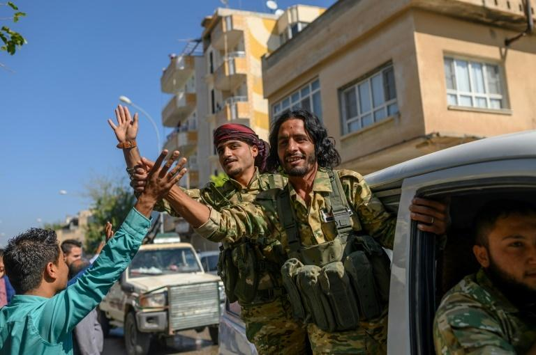 Dozens of vehicles carrying former Syrian rebels allied with Ankara have crossed the border into Syria to cheers from Turkish onlookers