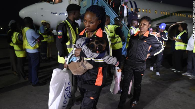 A mother and child return home to Lagos along with 150 other migrants from Libya