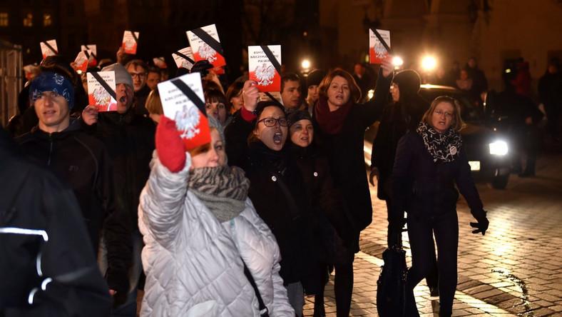 Kilkunastoosobowa grupa demonstrantów z KOD z egzemplarzami konstytucji