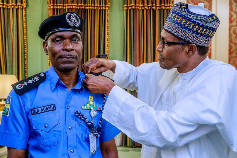 President Muhammadu Buhari decorates Mohammed Adamu as the new Inspector-General of Police [Twitter/@NGRPresident]