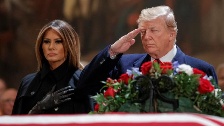 President Donald Trump with the first lady, Melania Trump, near the casket containing the body of former US President George H.W. Bush in the Rotunda of the US Capitol.