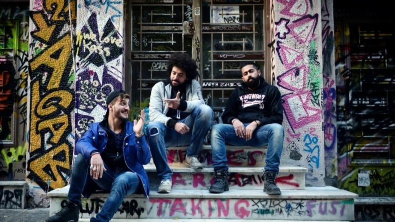 Syrian refugees from Aleppo (from L) Abu Habib, 24, Majd Ahmad, 26, and Abu Rmosh, 30, seen at the 'alternative' neighborhood of Exarchia in Athens, home to many Syrian refugees in NGO-leased apartments or in squats run by anarchist movements