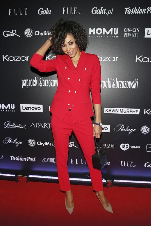 Omenaa Mensah dwurzędowy czerwony garnitur nosi z cielistymi szpilkami i małą czarną torebką