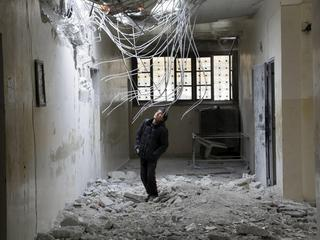 A boy inspects damage inside his school, due to what activists said was an air strike carried out ye