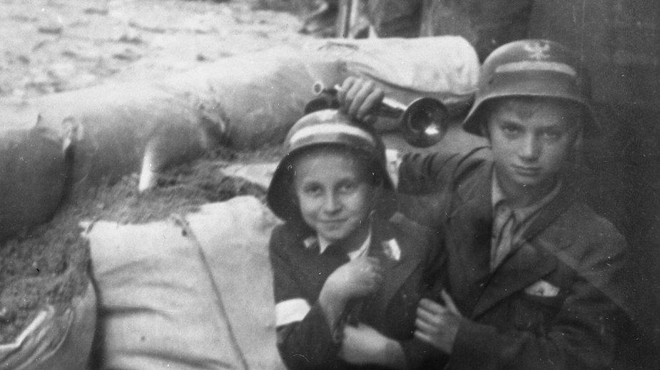 Dwoje dzieci przy workach z piaskiem w bramie gmachu zarządu Towarzystwa Zakładów Gazowych przy ul. Kredytowej 3 (Fot. Joachim Joachimczyk, ps. Joachim, zbiory MPW)