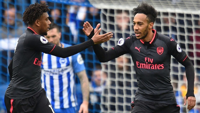 Arsenal's Gabonese striker Pierre-Emerick Aubameyang (R) celebrates with Arsenal's Nigerian striker Alex Iwobi after scoring their first goal during the English Premier League football match between Brighton and Hove Albion and Arsenal at the American Express Community Stadium in Brighton, southern England on March 4, 2018.