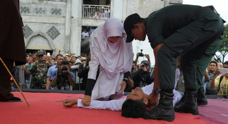 An Acehnese man collapses as he is caned by a religious officer in Banda Aceh on 27th February 2017