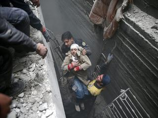 Syria Civil Defence members help an unconscious woman from a shelter in the besieged town of Douma