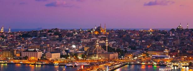 """W Stambule Europa spotyka się z Azją. To niezwykłe miasto o ponad 2500 letniej historii było stolicą trzech imperiów: rzymskiego, bizantyjskiego i osmańskiego. Chociaż dziś stolica Turcji znajduje się w Ankarze, to Stambuł pozostał miejscem, które trzeba zobaczyć. Wśród zapierającej dech w piersiach starożytnej architektury odnajdziemy nowoczesne restauracje i tętniące życiem nocne kluby. Meczety, bazary oraz hammamy (tureckie łaźnie) nie pozwolą nudzić się żadnemu turyście. Warto zacząć wycieczkę od budzącego podziw Błękitnego Meczetu (Sultan Ahmet Camii), który widać z wielu punktów miasta. Następnie można się przespacerować po moście Galata. Nie należy także zapominać o przejrzeniu oferty tysięcy stoisk na Krytym Bazarze, który zaliczany jest do jednych z największych tureckich atrakcji turystycznych. W Stambule znajduje się historyczny budynek stacji kolejowej Sirkeci, który służył jako ostatni przystanek Simplon-Orient Ekspresu - """"króla pociągów i pociągu królów"""", kursującego pomiędzy Paryżem a Stambułem od 1883 do 1977 roku."""
