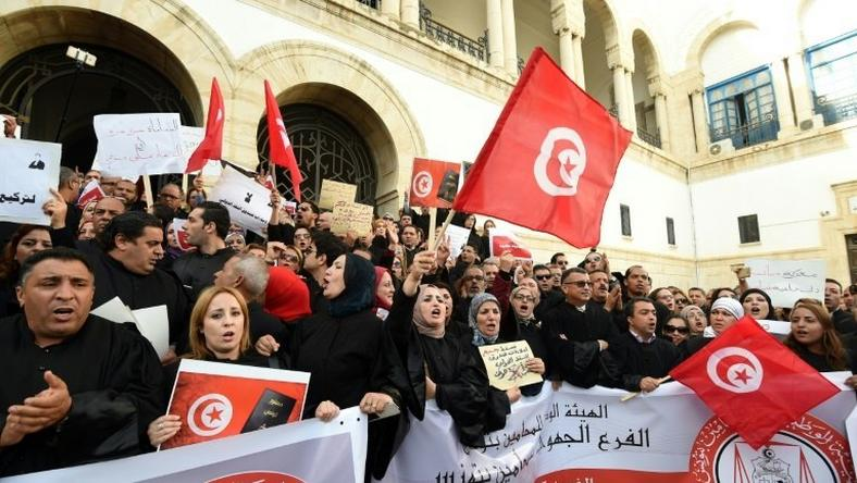 Tunisian lawyers shout anti-government slogans during a demonstration against a draft 2017 budget that would impose a public sector pay freeze on December 6, 2016 outside Tunis law court