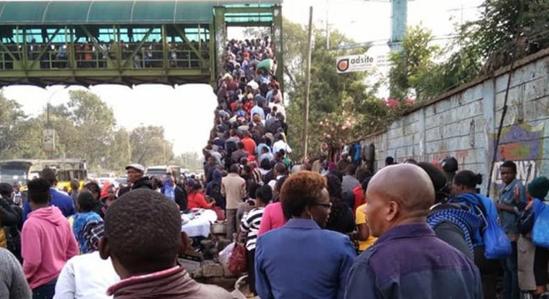 Kenyans walk after the ban of matatus from the CBD took effect