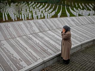 Bida Smajlovic, prays near the Memorial plaque with names of killed in Srebrenica massacre before wa