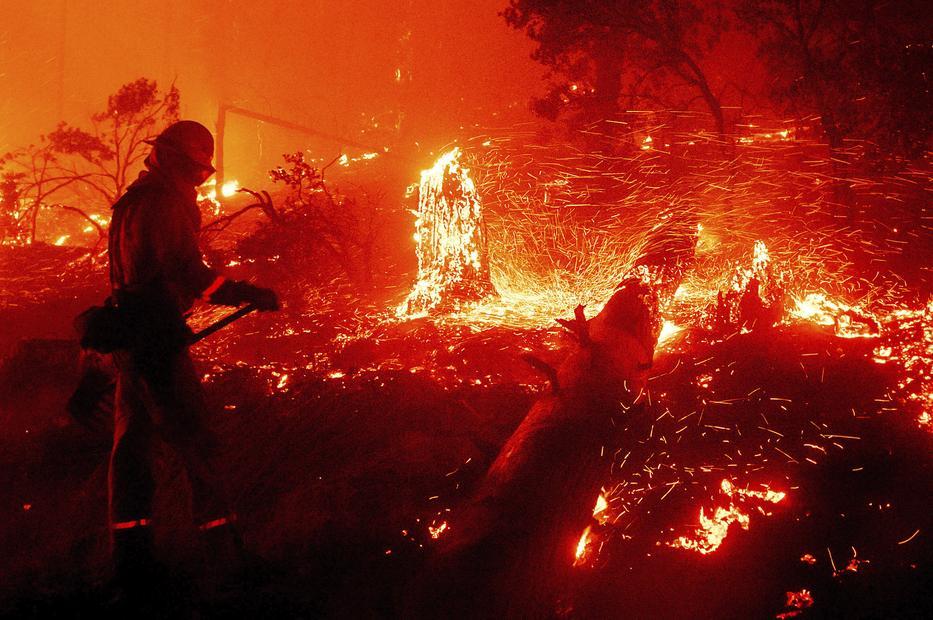 Tűzoltó küzd a lángok megfékezésén a kaliforniai Cascadel Woods közelében pusztító erdőtűz helyszínén / Fotó:MTI/AP/Noah Berger