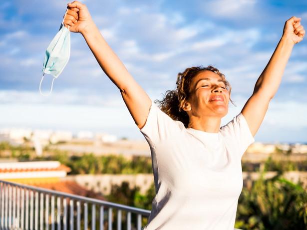 Kobieta trzyma maseczkę ochronną w ręku