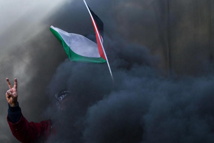 Protester holds a Palestinian flag as smoke rises from a burning tyre during clashes with Israeli tr