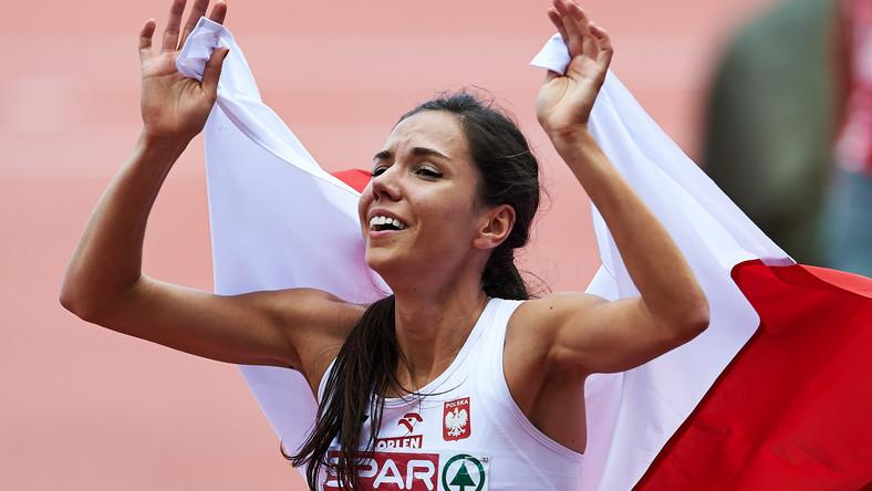 Owinięta w biało-czerwoną flagę Polka Joanna Jóźwik cieszy się po zdobyciu brązowego medalu w finałowym biegu kobiet na dystansie 800 metrów