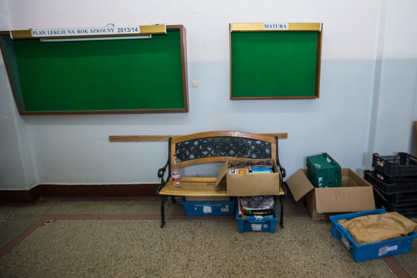 Korytarz szkolny z kartonami i tablicami