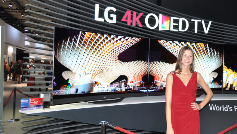 Piękna kobieta pokazuje piękny telewizor OLED 4K