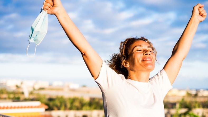 Szczęśliwa kobieta trzyma maseczkę ochronną w ręku