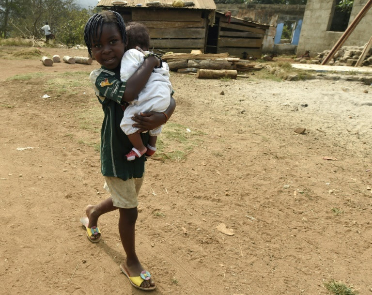 Boy walks with a baby in a local community in Rivers (AFP)
