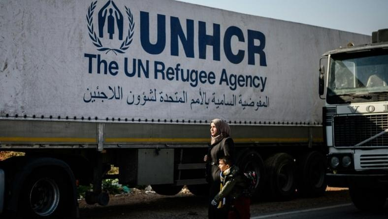 A Syrian woman with her child walks near a Syrian-bound truck loaded with humanitarian aids at the UN transhipment hub at Cilvegozu in Reyhanli near the Turkish-Syrian border in Hatay on November 28, 2016