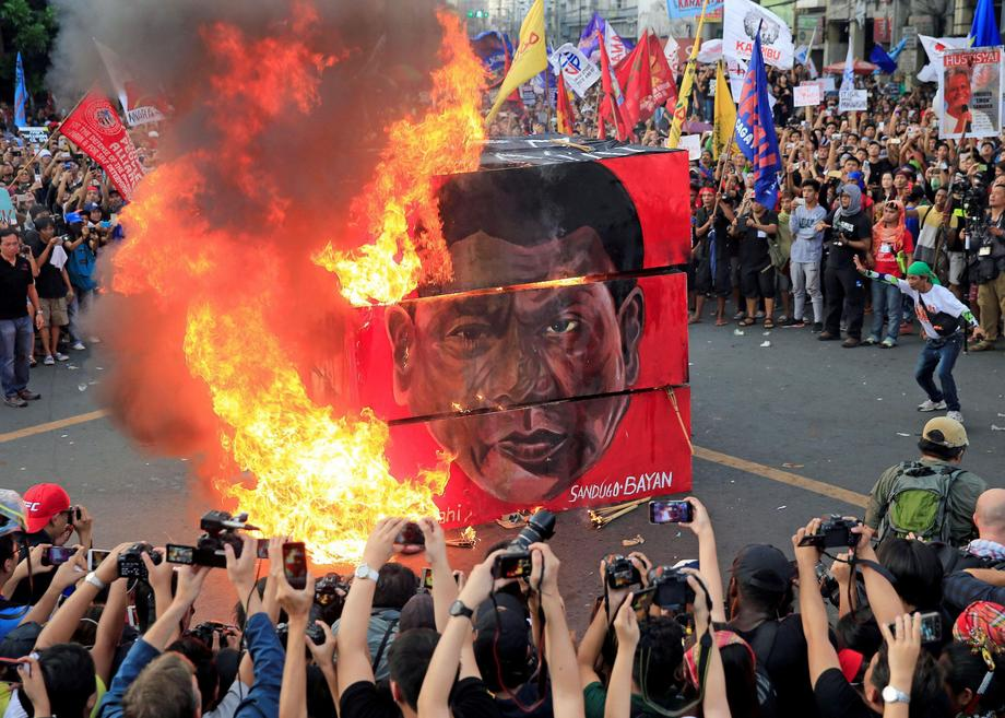 Protesters burn a cube effigy with a face of President Rodrigo Duterte during a National Day of Prot