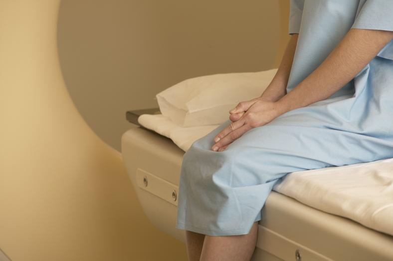 Female patient sitting nervously on scanner bed