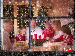 Family enjoying Christmas dinner at home in decorated room