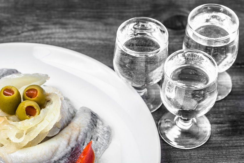 Marinated herring and vodka shot. Traditional polish appetizer.
